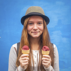 Funny hipster girl with ice cream in hand on the blue wall.