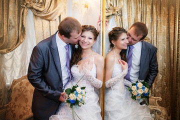groom and the bride stand near a mirror with a gold frame
