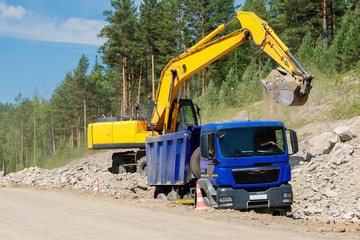 Dump Truck and Excavator in a Quarry. Building of the road.