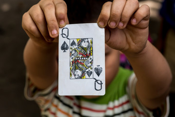 child showing poker card, black queen