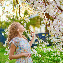Young woman in cherry blossom garden