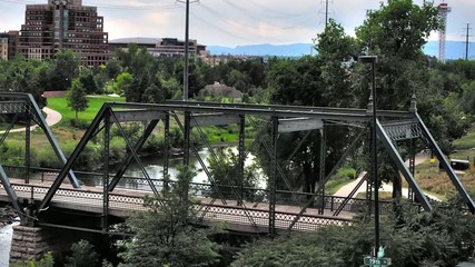 Zoom in from an urban park to an old iron bridge