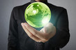 holding a glowing earth globe in his hands. Earth image provided