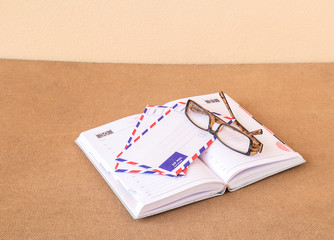 Notebook, glasses and envelope on a wood background
