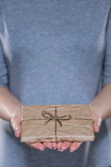 Female hands with simple wrapped gift