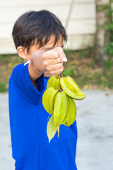 Boy give a Carambola or star  fruit from garden