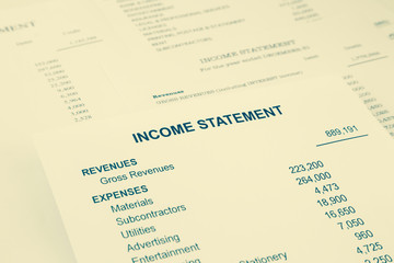 Income statement reports for business accounting in sepia tone