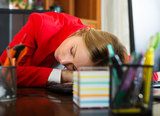 tired businesswoman sleeping at office desk