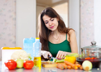 beautiful housewife cutting vegetables at  kitchen
