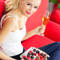 Cheerful woman with sweets and champagne
