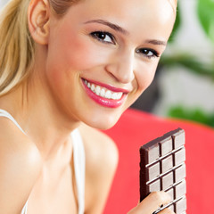 Woman eating chocolate at home