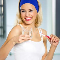Cheerful woman bruhing teeth
