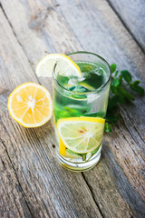 Lemonade with fresh lemon and mint in glass on wooden background