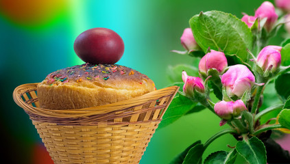 Easter cakes and red Easter egg beside a blossoming Apple tree.