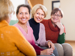 Smiling female pensioners on sofa