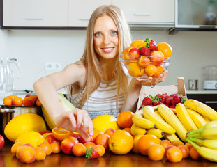 Happy  long-haired woman taking fruits from table