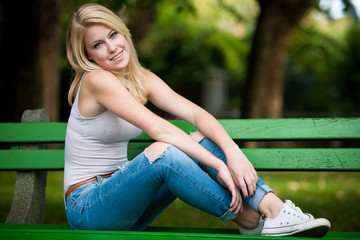 Beautiful blonde woamn rests on a bench in park