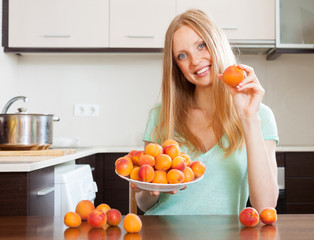 blonde girl near heap of apricots at home kitchen