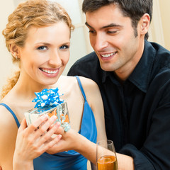 Couple celebrating with gift and champagne