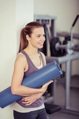 frau mit yogamatte im fitness-studio