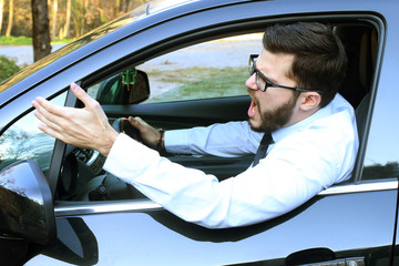 angry man driving a car and raising his hand violently