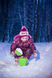 Adorable girl ride on ski and play with snow in evening park
