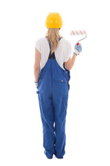 back view of young woman painter in blue builder uniform with pa