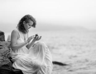 Portrait of a woman holding zen stones in hand.