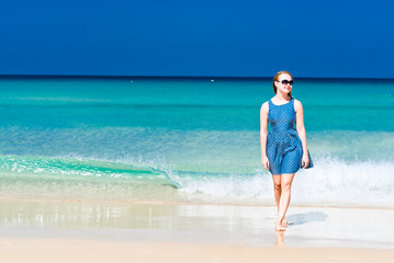 Young woman wearing a blue dress walking on a beach