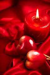 Valentine's Day. Valentine red hearts and candle on red silk