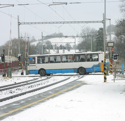 A bus on a railway crossing during snow storm