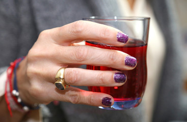 woman's hand that holds the glass during the aperitif