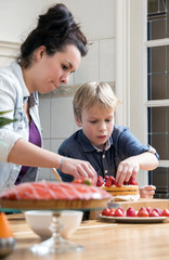 Mother And Son Preparing Cake In Kitchen