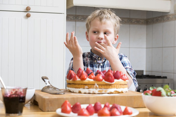 Boy Licking Finger with Strawberry Cake batter behind a kitchen