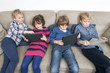 Brothers And Sister Using Digital Tablets On Sofa