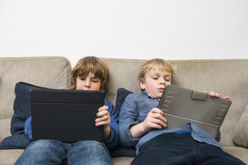 Boys Using Digital Tablets On Sofa