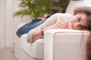 young pretty girl lying on a couch and smiling