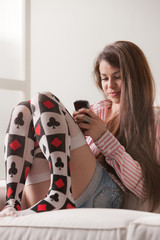 teen girl on a sofa texting with her phone