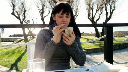 Woman having breakfast in front of sea texting message