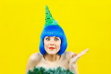 girl in a blue wig and in a Christmas cap on a yellow background