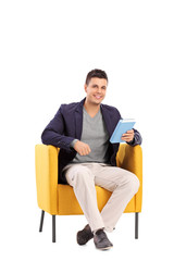 Man holding a book seated in an armchair