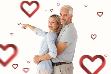 Composite image of happy couple smiling at camera and pointing