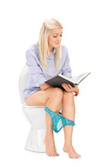 Woman peacefully reading a book seated on toilet