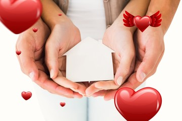 Composite image of couple holding miniature house in hands