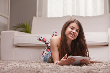 girl with a tablet on the carpet in her living room