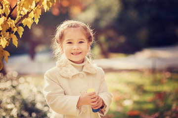 Baby girl laughing in the autumn on outdoors