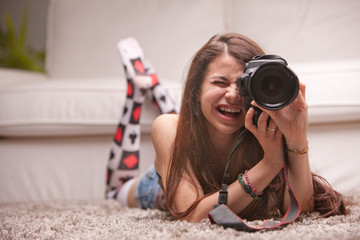 beautiful girl taking photographs at home