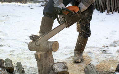 The process of cutting firewood with chainsaw outdoors