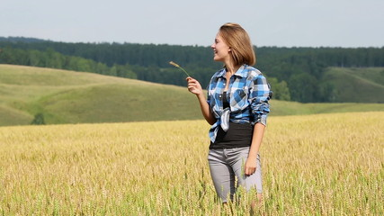 Young woman in field of wheat, tasting the spikelet