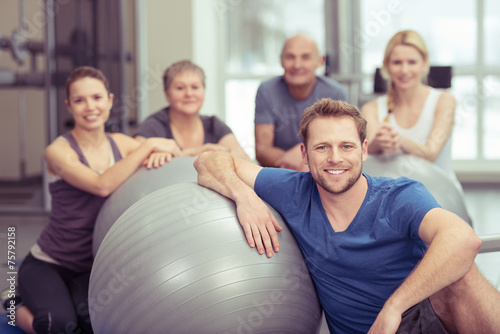 trainer mit einer gruppe im fitness-studio - 75792158
